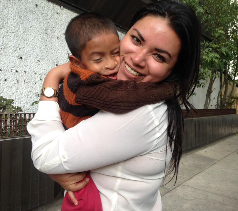 Karla holding a small patient as he hugs her around the neck
